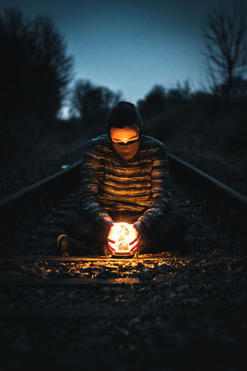 Man with illuminated lighting equipment sitting on railroad tracks during dusk