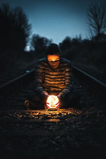 Man With Illuminated Lighting Equipment Sitting On Railroad Tracks During Dusk