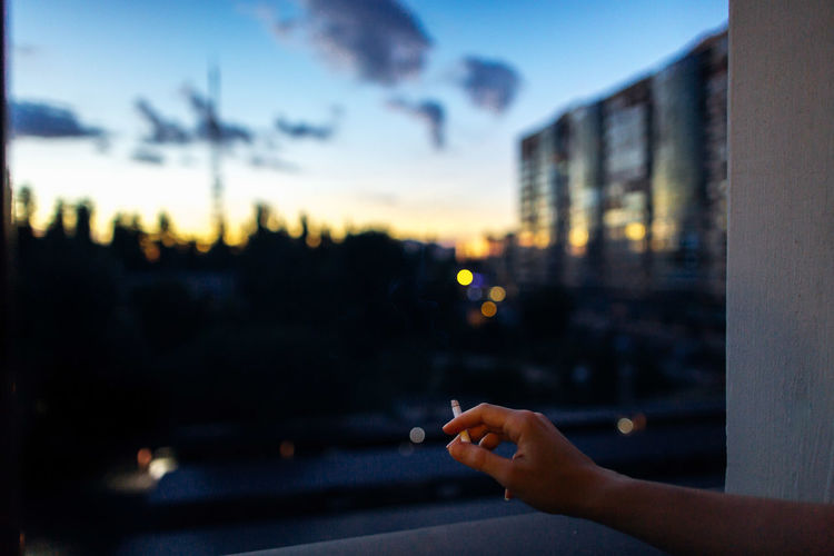 Close-up of woman hand holding city against sky during sunset