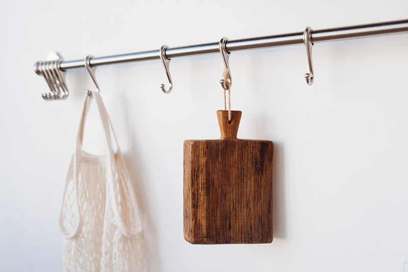 Close-up of clothespins hanging on clothesline against wall