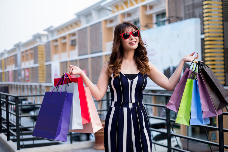 Portrait of smiling young woman with colorful shopping bags standing on bridge