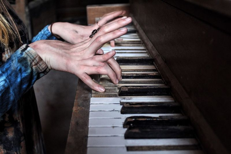 Midsection Of Woman Playing Abandoned Piano