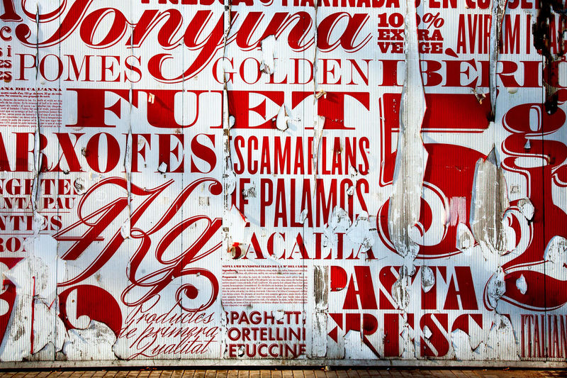 Torn posters on outside of market, Barcelona, Spain. Arxofa Barcelona Catalan Language City Colourful Day Fuet Graphic No People Outdoors Post Red Scamallans Text Toronto