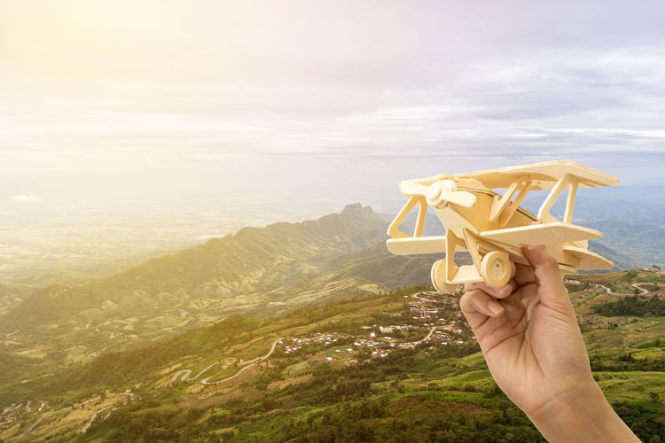 Cropped hand of person holding toy plane against mountains