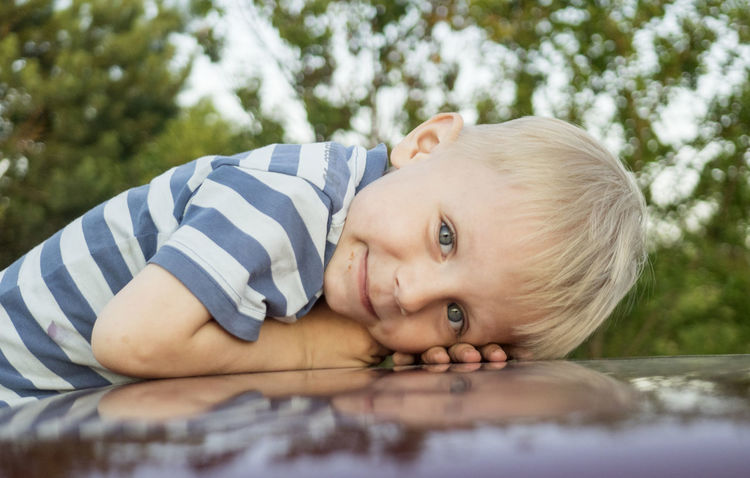Happy Caucasian boy lies on car roof and looks at camera Happy Looking At Camera Roof Blond Hair Boys Car Casual Clothing Caucasian Childhood Close-up Cute Day Front View Headshot Innocence Leisure Activity Lies Lifestyles Looking At Camera Looks At Camera Lying Down Nature One Boy Only One Person Outdoors People Portrait Real People Smiling Striped