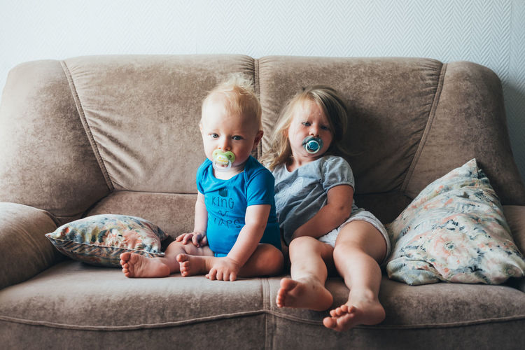 Portrait of siblings with pacifiers sitting on sofa at home
