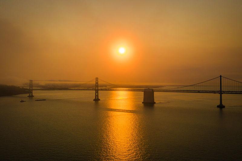 Silhouette bridge over sea against orange sky
