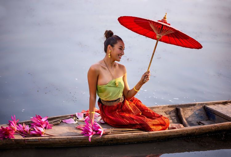 Woman holding umbrella by louts while sitting on boat in lake