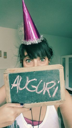 Portrait of woman with party hat holding writing slate at home