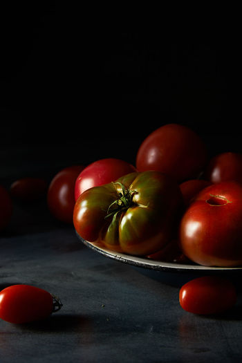 Heirloom Tomatoes Black Background Close-up Dark And Moody Dark Food Photography Food Freshness Group Of Objects Healthy Eating Indoors  No People Red Ripe Still Life Studio Shot Table Tomato Vegetable Wellbeing Wood - Material