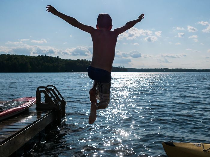 The joy of childhood. Cottage Life Kayak Paddle Board Dock Silhouette Boy Lake Water Real People Leisure Activity Human Arm One Person Sky Lifestyles Jumping Mid-air Enjoyment Full Length Freedom Arms Raised Outdoors The Great Outdoors - 2018 EyeEm Awards