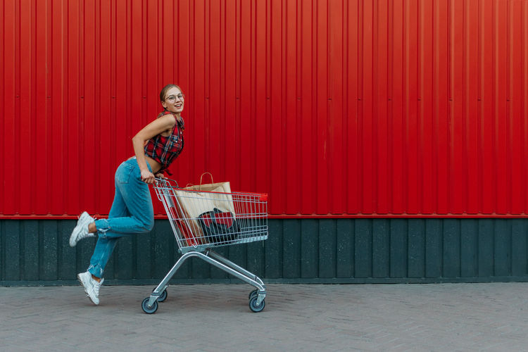 Happy girl with shopping cart on red wall shop background. young woman pushing a shopping cart