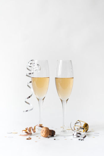 Close-up of wine glasses on table against white background