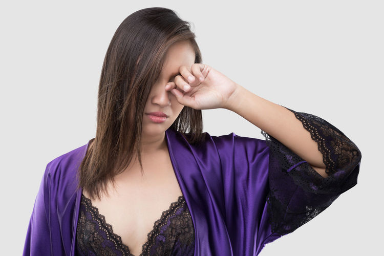 The woman in silk purple nightgown and lace robe rubs her eye with a finger against the gray background, Women in violet satin nightwear have itching in the eye Itching Itch Itchy EyeEmNewHere Rubbing Rubbing Eyes Rubbing Face Sleepy Lazy SORE Pain Ache Sadness Sad Strain Allergies Tired Nightgown Purple Robe Silk Satin Inflammation Studio Shot One Person Young Adult Young Women Indoors  White Background Front View Cut Out Women Lifestyles Casual Clothing Adult Standing Hairstyle Portrait Beauty Hand Beautiful Woman