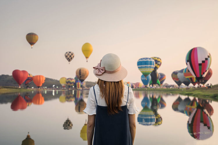Rear view of woman standing by lake with balloons flying against sky