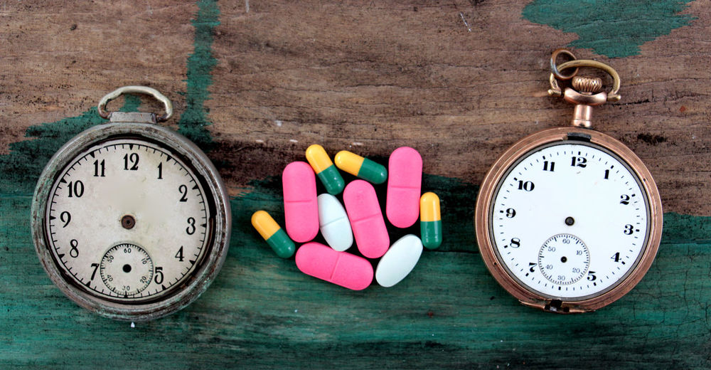 High angle view of damaged pocket watches with pills on table