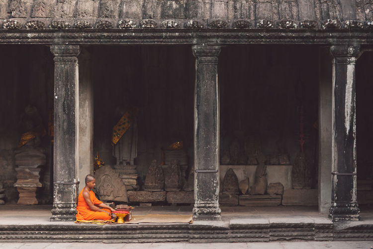 Siem Reap Cambodia Angkor Angkor Wat Angkor Wat, Cambodia Architecture Religion Spirituality Built Structure Place Of Worship Belief Real People Sitting One Person Building Exterior Traditional Clothing Building Full Length History Day Clothing The Past Architectural Column Outdoors