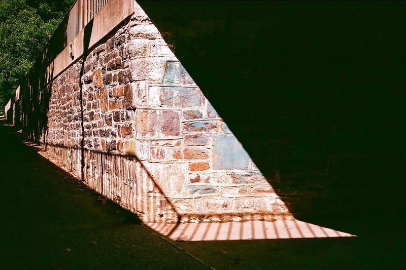 A brick wall and shadow play with railing in the afternoon sun Design Web Banner Backgrounds Sunlight And Shadow Foot Path Path Tunnel Shadow Play Textured  Textured  Diminishing Perspective Perspective Point Of View Environment EyeEm Selects Nature No People Architecture Built Structure Plant Day Outdoors Tranquility Beauty In Nature Sunlight Building Exterior Staircase Wall Tranquil Scene Pattern