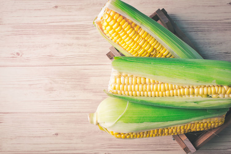 fresh raw sweet corn on the cob kernels over wooden background Table Corn Food And Drink Wood - Material Still Life Food Vegetable Healthy Eating Wellbeing Freshness High Angle View Corn On The Cob Green Color Yellow Indoors  Close-up Sweetcorn No People Directly Above Day Wood Grain Snack