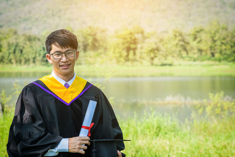 Portrait of smiling young man in graduation gown