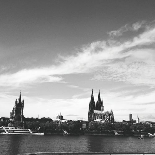 Churches in city by rhine river against sky