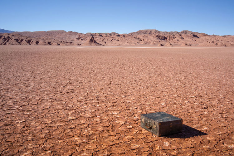 Old leather suitcase in the barren and rocky desert on sunny day