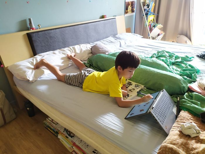 Boy lying on bed at home