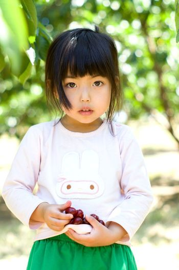 Portrait of cute girl holding fruits