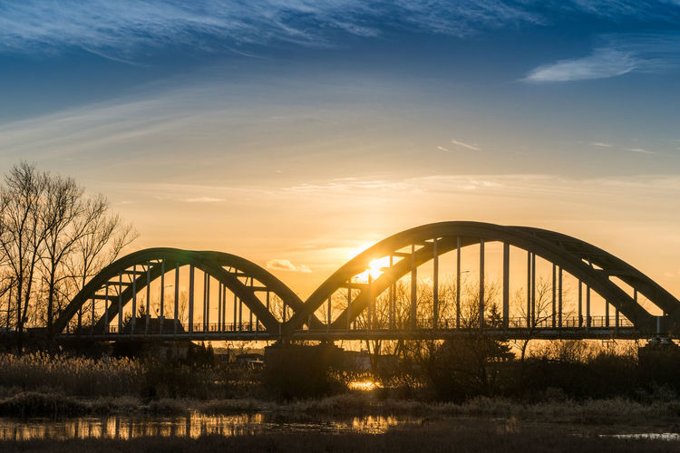 Metal arcs bridge over a river on sunset Arch Architecture Beauty In Nature Bridge - Man Made Structure Built Structure Connection Dawn Day Nature No People Orange Color Outdoors River Scenics Sky Sunset Transportation Travel Destinations Tree Water