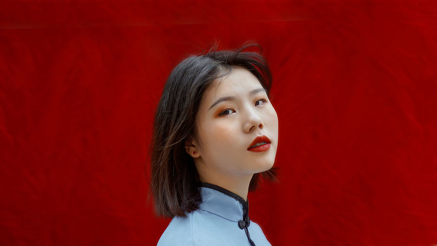 Portrait of young woman against red wall