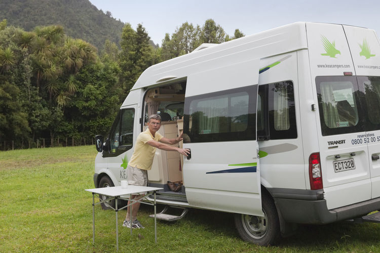 Man opening door of campervan on a campground in the Kauaeranga Valley, Coromandel, New Zealand. Camping Ford Ford Transit Man Tourist Transportation Travel Camper Camper Van Campervan Campground Campinglife Grass Kea Land Vehicle Men New Zealand One Man Only Outdoors People Real People Recreational Vehicle Rv Stationary Tourism