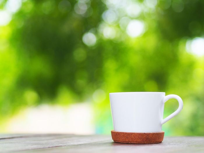 Coffee cup over green leaf background. Close-up Coffee Coffee - Drink Coffee Cup Copy Space Crockery Cup Day Drink Focus On Foreground Food And Drink Freshness Hot Drink Mug No People Non-alcoholic Beverage Outdoors Plant Refreshment Single Object Table Tea Cup Tree Wood - Material