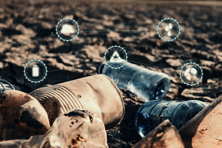 Close up bottle plastic with icon on crack ground beside the lake outdoor on the baking hot day, Drought and environmental problems. Close-up Nature Outdoors Day Hot Drought Environment Problem Protection Garbage Bottle Icon Selective Focus Land Container Pollution