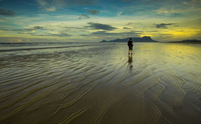 man at beach during sunset Ankle Deep In Water Beach Beauty In Nature Cloud - Sky Day Full Length Horizon Over Water Leisure Activity Lifestyles Nature One Person Outdoors People Real People Rear View Sand Scenics Sea Sky Standing Sunset Tranquil Scene Tranquility Water Women
