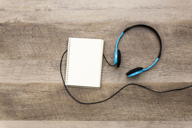 High angle view of headphones with book on table