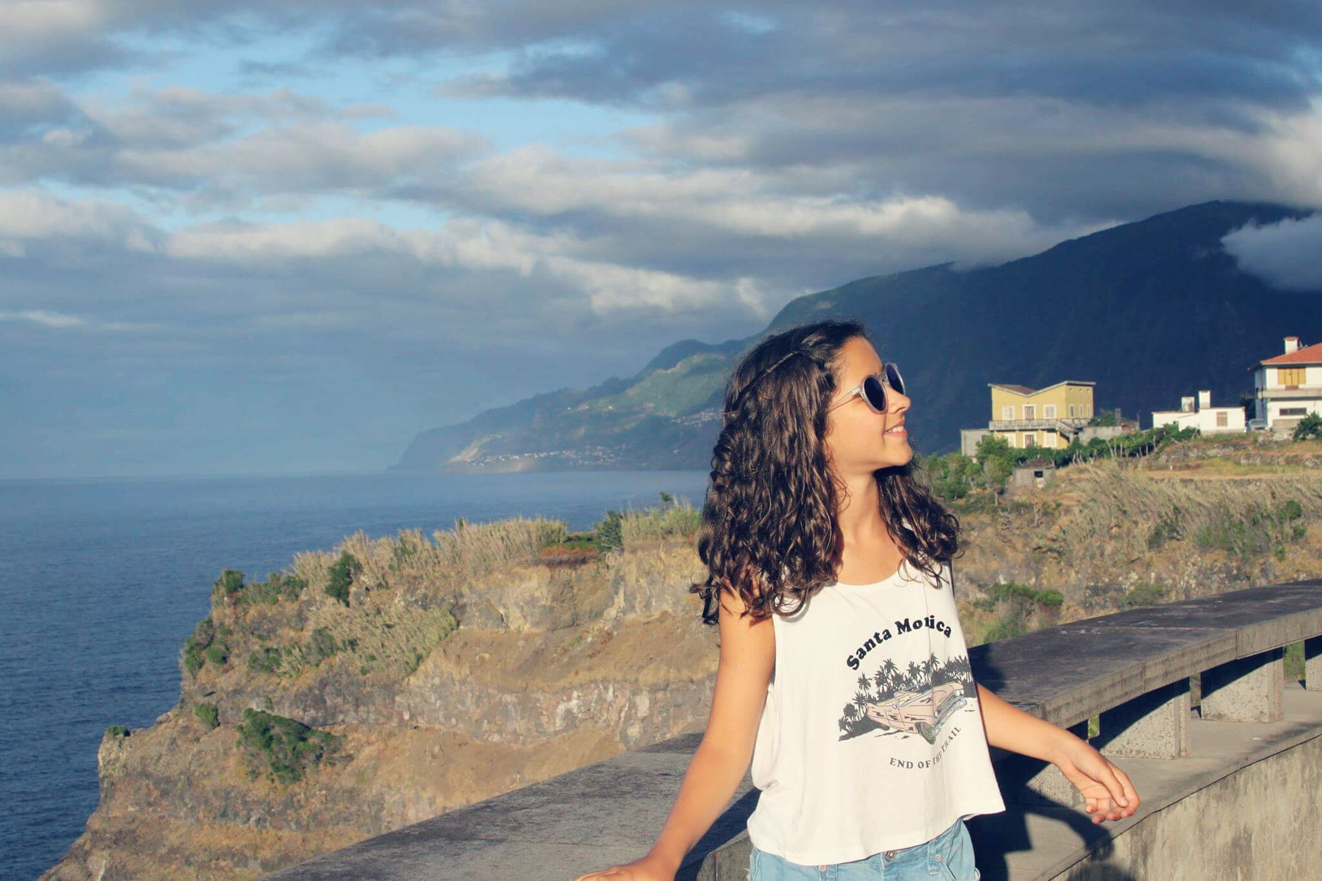 sea, water, standing, young women, young adult, leisure activity, sky, lifestyles, casual clothing, person, long hair, horizon over water, scenics, mountain, vacations, cliff, beauty in nature, tranquil scene, nature, summer, tranquility, weekend activities, enjoyment, day, cloud - sky
