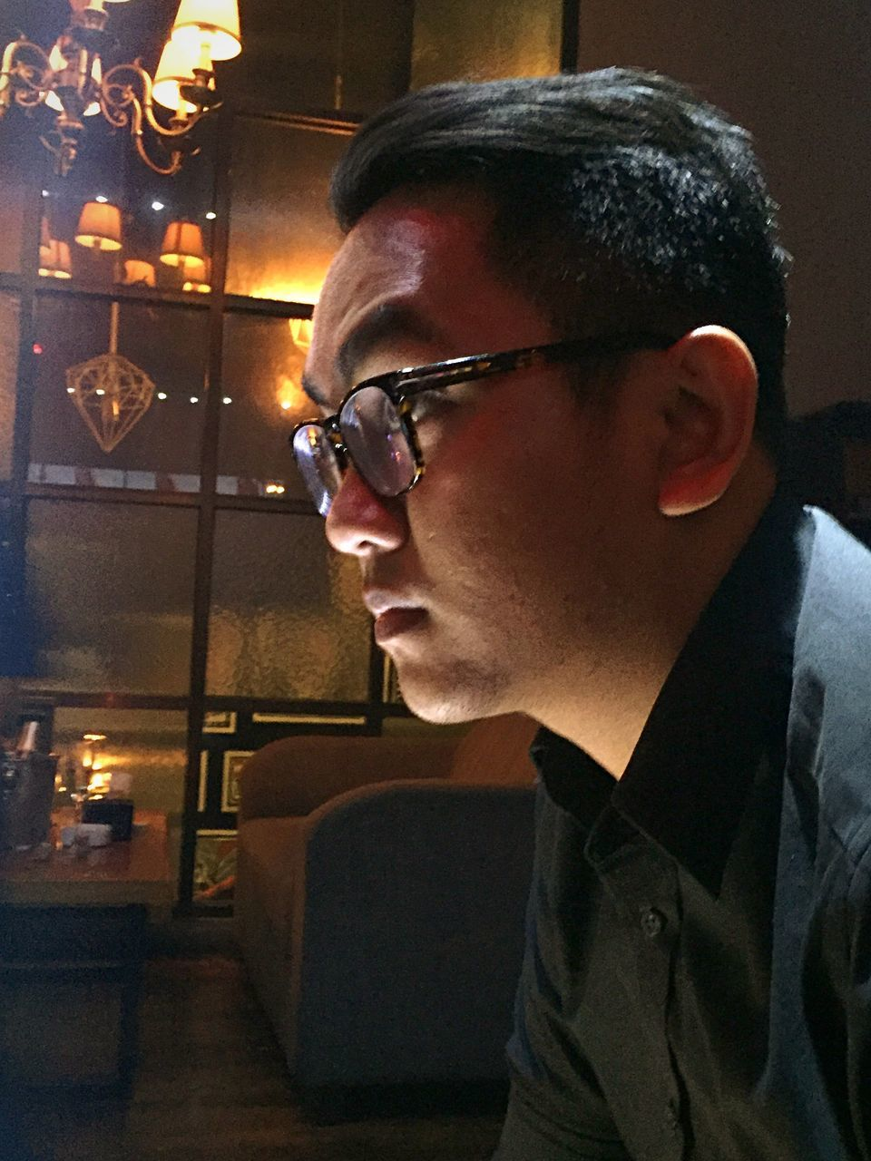 real people, one person, young adult, young men, glasses, indoors, night, eyeglasses, leisure activity, lifestyles, illuminated, close-up