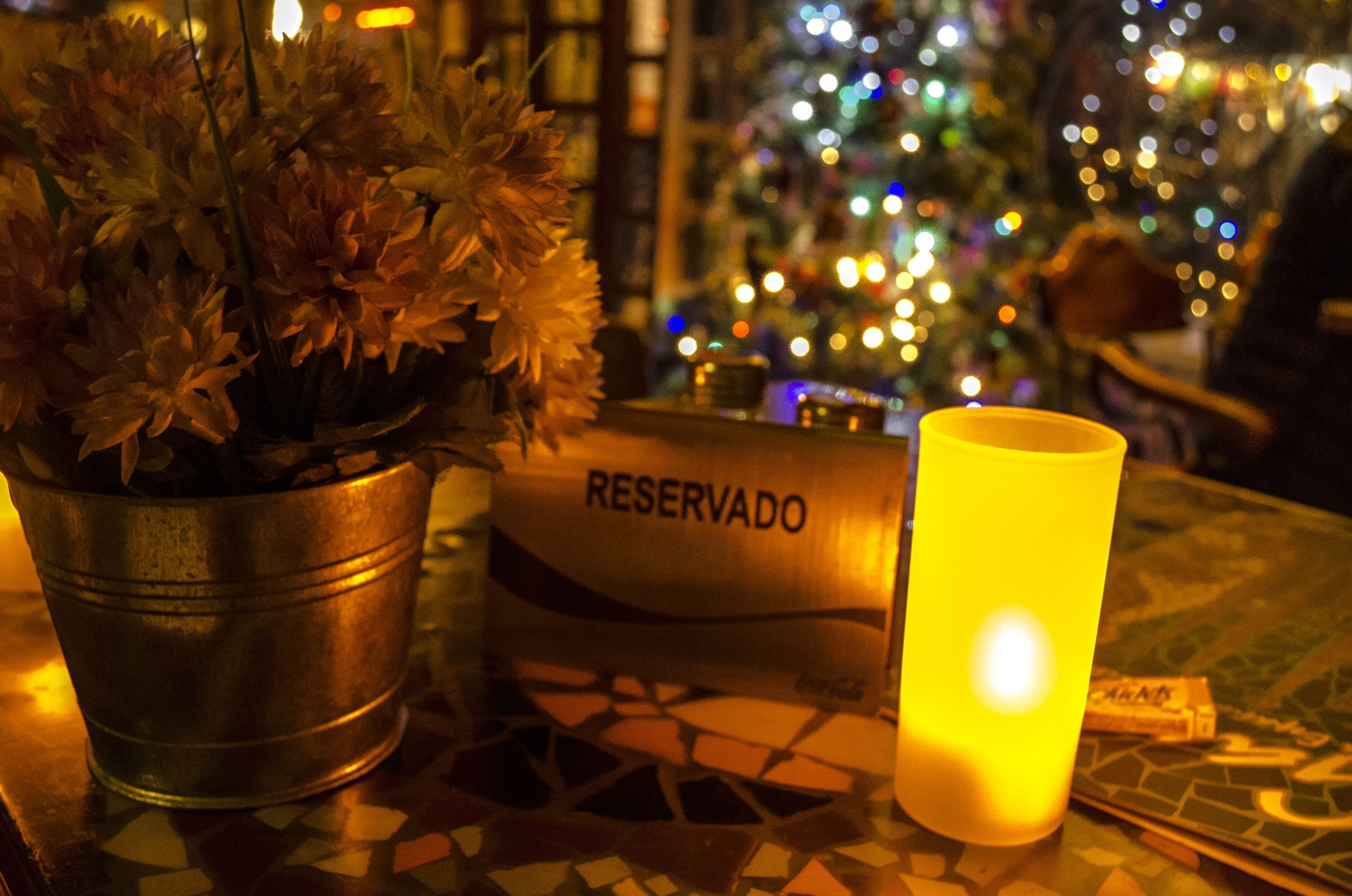 drink, illuminated, text, food and drink, table, focus on foreground, close-up, tree, communication, night, refreshment, western script, yellow, glass - material, restaurant, no people, candle, outdoors, growth