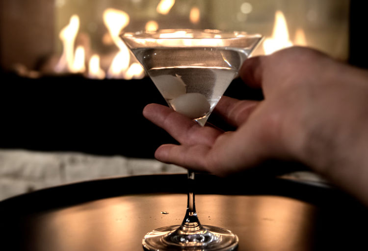 Cropped image of hand holding martini glass on tray against fireplace
