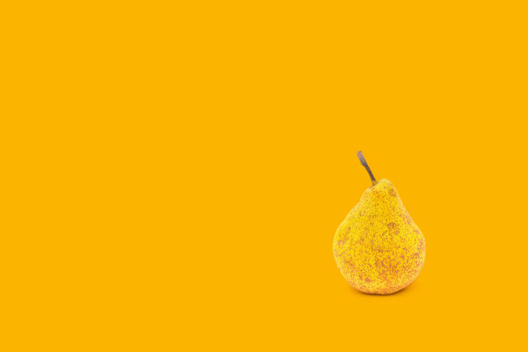 Pear on Yellow background Poster Yellow Studio Shot Healthy Eating Food And Drink Food Fruit Copy Space Wellbeing Single Object Indoors  Freshness Colored Background No People Cut Out Close-up Pear Still Life Orange Color Yellow Background Ripe