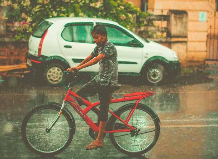 Boy riding bicycle on road during rainy season