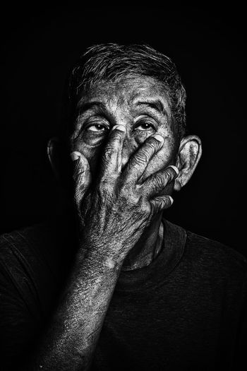 Close-up of hand covering mouth while looking away against black background