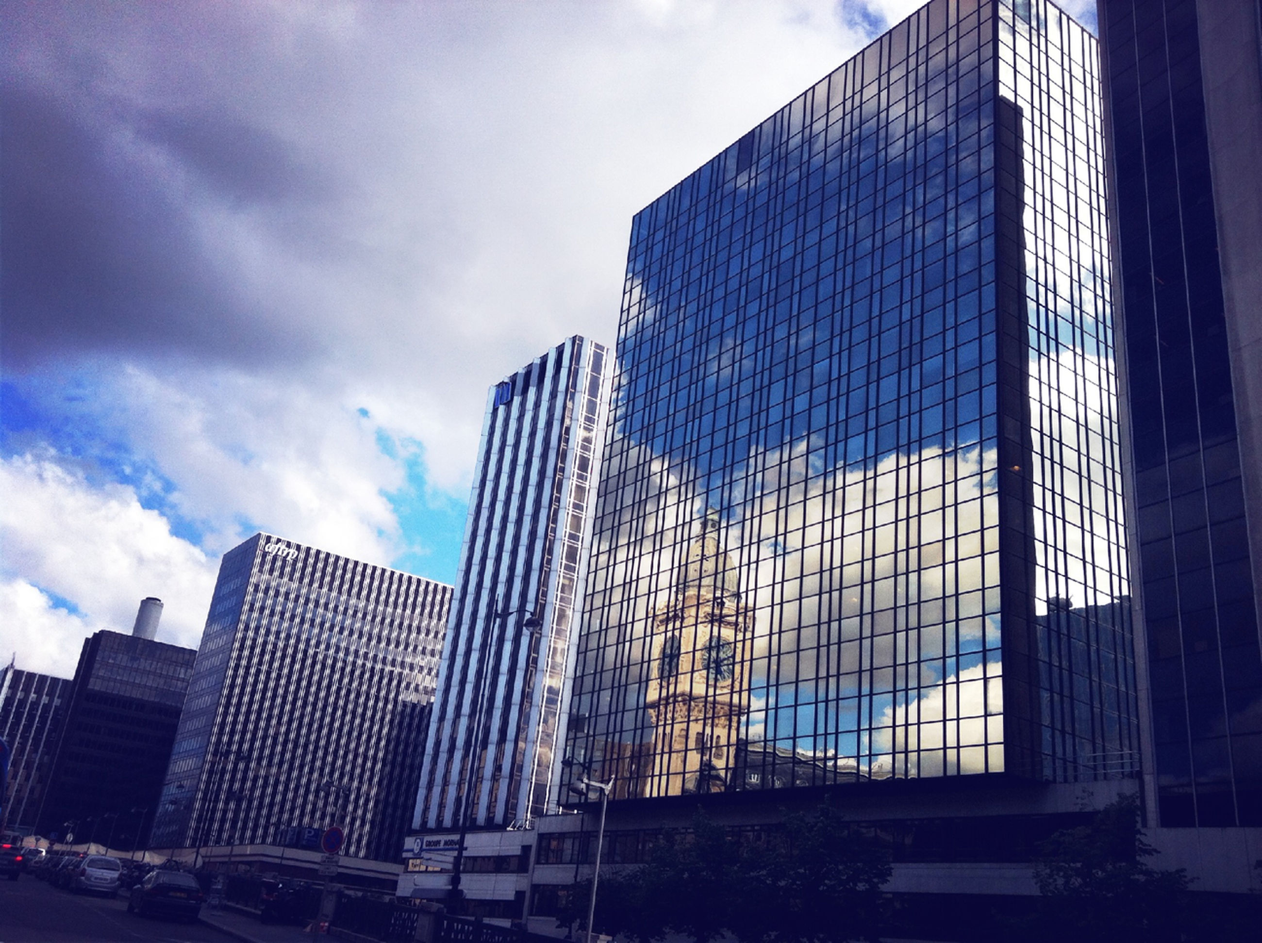 architecture, built structure, building exterior, city, modern, skyscraper, sky, office building, low angle view, tall - high, tower, cloud - sky, glass - material, capital cities, building, cloud, travel destinations, famous place, city life, day