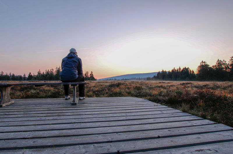 Rear view of man on walkway at sunset