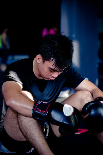 Close-up of boxer looking down while sitting in gym