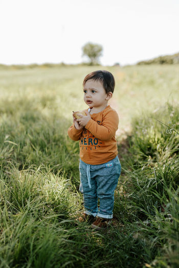 Cute boy standing on field
