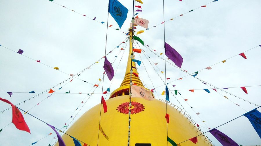 Low angle view of colorful flags decorated on temple against sky