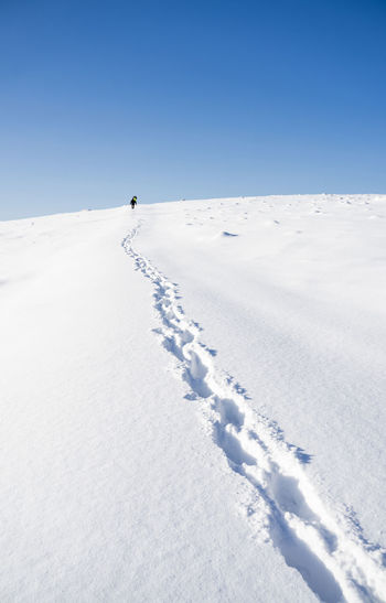Person skiing on snow covered land against sky