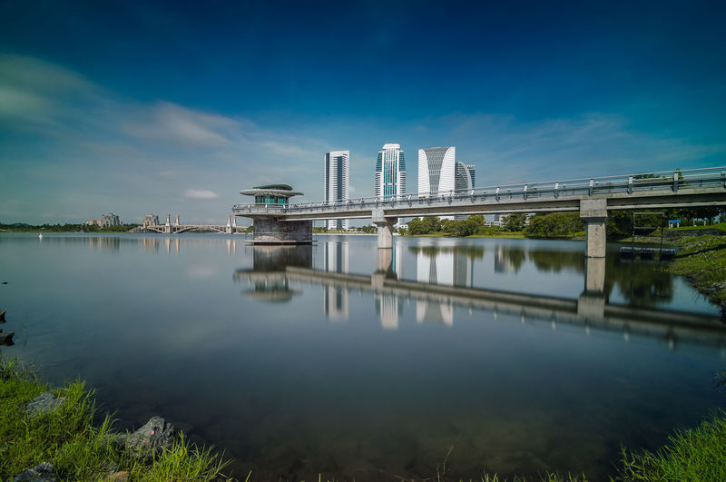 Modern Government Buildings And Jetty Reflection In Lake Against Sky