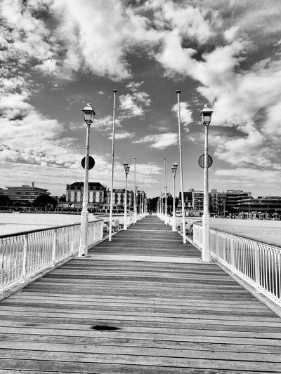 Empty footpath by pier against sky